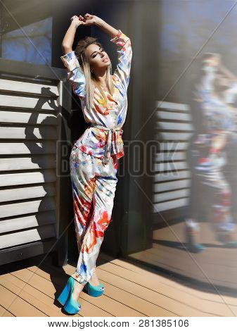 Trendy Lady Enjoys The Warm Sun Rays Outdoor Near The House, Raised Her Hands Up. Wearing Summer Sui