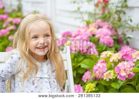 New Life Concept. Spring Holiday. Childrens Day. Small Baby Girl. Little Girl At Blooming Flower. Su