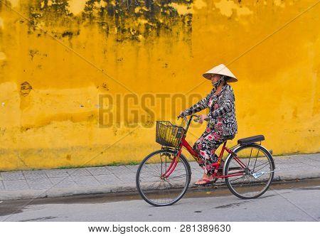 Hoi An, Vietnam - Jan 20, 2019. An Old Woman Biking On Street In Hoi An Old Town, Vietnam. Hoi An Is