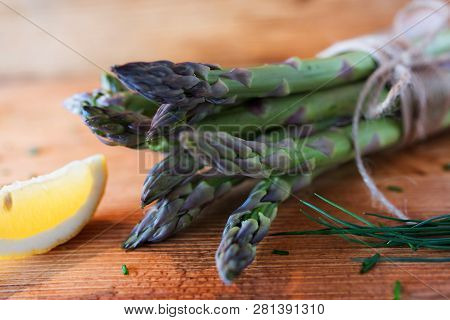 Bunch Of Fresh Green Asparagus With Lemon And Chive On Rustic Wooden Table