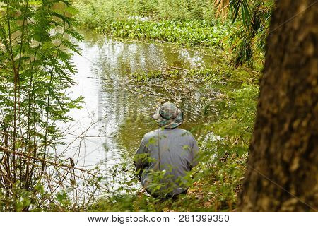 Man In A Hat Throws A Fishing Rod On A Small Pond, Fishing In The Pond