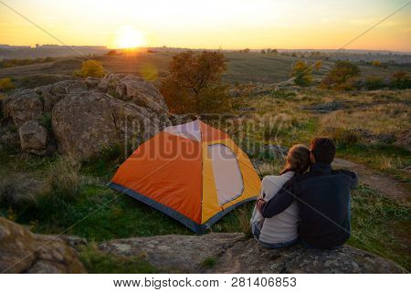 Young Couple Sitting near Tent and Watching Beautirul Sunset in the Mountains. Adventure and Family Travel Concept.