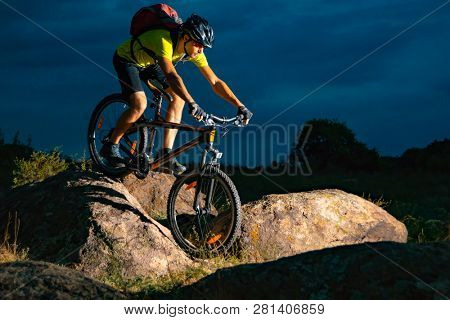 Cyclist Riding the Mountain Bike on the Rocky Trail in the Evening. Extreme Sport and Enduro Biking Concept.