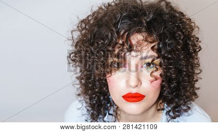 Close-up Portrait Of Beautiful Young Woman With Afro Hairstyle On White Background. Kinky Girl With