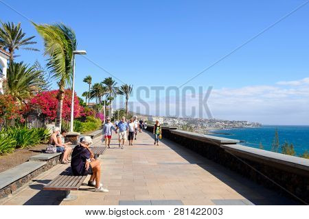 MASPALOMAS, SPAIN - JANUARY 23, 2019: Vacationers at the promenade of Playa del Ingles, in Maspalomas, in the Canary Islands, Spain, a popular winter beach destination for European people