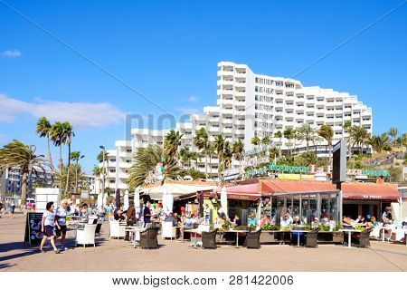 MASPALOMAS, SPAIN - JANUARY 23, 2019: Vacationers at the restaurant terraces of Playa del Ingles, in Maspalomas, in the Canary Islands, Spain, a popular winter beach destination for European people