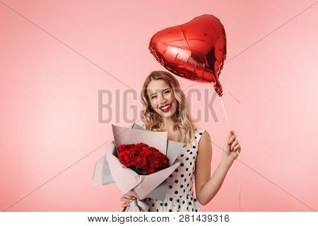 Beautiful young blonde woman wearing dress standing isolated over pink background, holding bouquet of roses and a heart shaped balloon