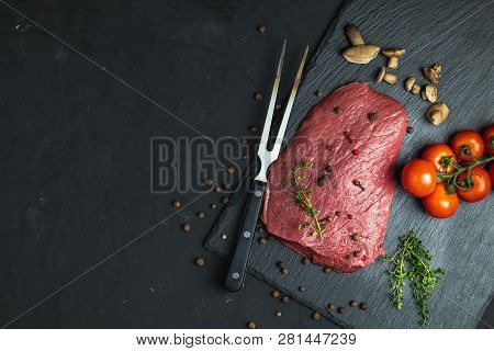 Fresh Raw Meat Beef Steak With Ingredients For Cooking Spices, Thyme, Tomatoes And Mushrooms On Dark