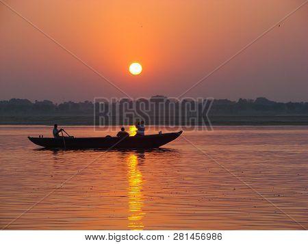 Pilgrims Floating By Boat Of The Sacred Ganges River. Sunrise In Varanasi. Uttar Pradesh, India.