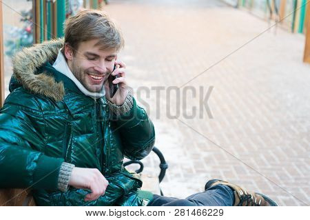 Man Handsome Hold Smartphone. Man Unshaven Wear Warm Jacket And Hold Smartphone Snowy Urban Backgrou
