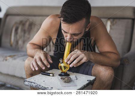Young Man Smoking Pot Using Bong; Man Inhaling Marijuana Vapor From A Bong