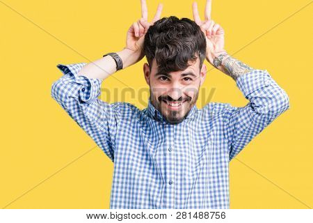 Young handsome business man over isolated background Posing funny and crazy with fingers on head as bunny ears, smiling cheerful