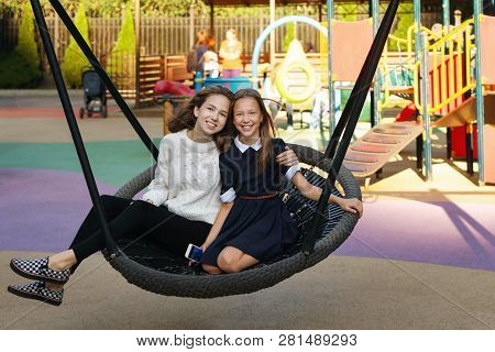 Two Cute Teen Sisters Ride On Swing Together. Leisure Time. Rest After School Classes.