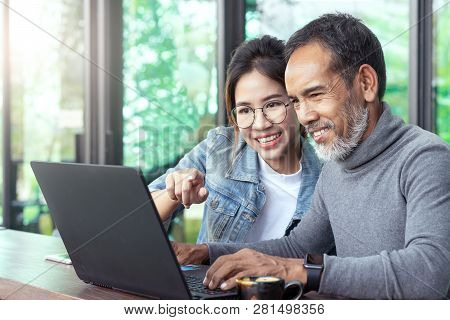 Attractive Mature Asian Man With White Stylish Short Beard Looking At Laptop Computer With Teenage E