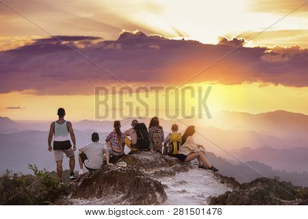 Big Group Of Friends Stands On Mountain Top And Looks At Beautiful Sunset. Travel With Friends Conce