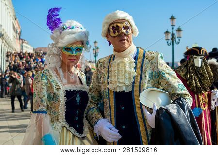 VENICE, ITALY - FEBRUARY 18, 2017: Couple of unidentified participants in vintage colorful costumes and masks during famous traditional Carnival taking place each year on february in Venice, Italy.