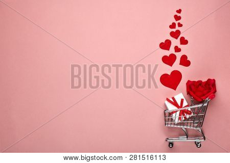Shopping trolley, gift box, flower and decorative red hearts on pink background with copy space. Valentine's day, Mother's day,  wedding