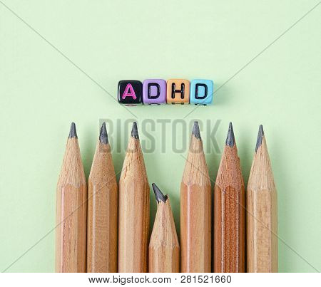 Attention Deficit Hyperactivity Disorder Or Adhd Concept With Wooden Pencil On Green Background.