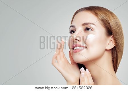 Young Beautiful Woman With Healthy Clear Skin Applying Moisturizing Cream On Her Face On White Backg