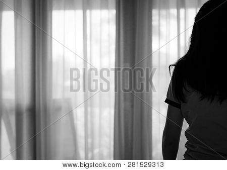 Rear View Of Sad Adult Asian Woman Sit On Bed In Bedroom. Stressed And Depressed Young Woman. Despai