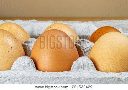 Close Up Of Chicken Eggs In A Carton Box On A Table.