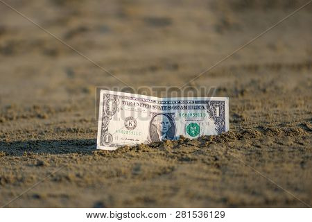 Banknote Of Value Of One Dollar In The The Sand On The Beach. Concept Of Cheap Travel And Vacation.