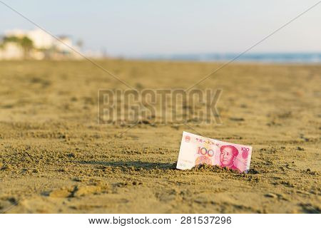 Banknote Of Value Of Of An China Yuan In The The Sand On The Beach. Concept Of Cheap Travel Insuranc