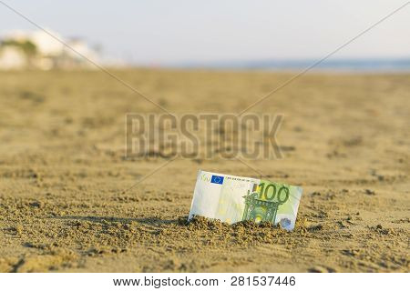 Banknote Of Value Of One Hundred Euro In The The Sand On The Beach. Concept Of Cheap Travel And Vaca