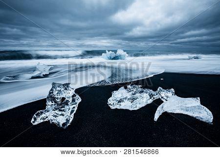 Incredible piece of the iceberg sparkle on black sand. Location Jokulsarlon lagoon, Diamond beach, Vatnajokull national park, Iceland, Europe. Popular tourist attraction. Discover the beauty of earth.