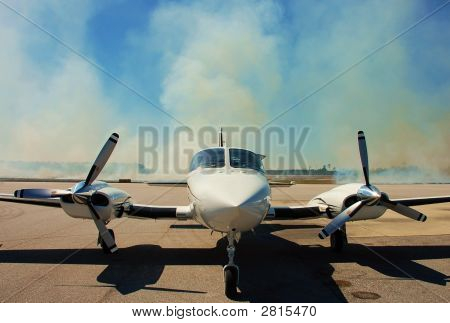 Twin engine Cessna 421 parked on the ramp with burning grass in the background poster