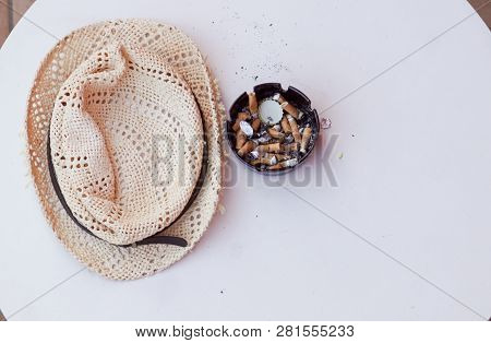Top View Of Cigarette Ends And Ash In Filthy Ashtray On Wooden Table