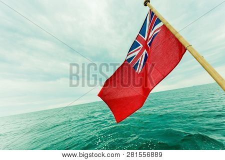 The uk red ensign the british maritime flag flown from yacht sail boat, blue sky and baltic sea. Summer and travel voyage poster