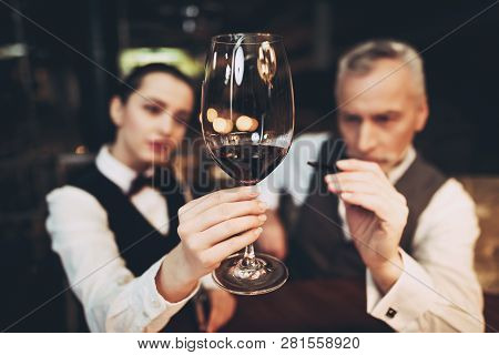 Sommelier Is Studying Sediments In Glass Of Wine.waiter Holds Glass Of Red Wine. Wine Tasting. Check