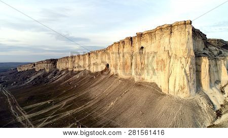 Top View Of Sheer Cliff. Shot. Amazing Panoramic View Of Steep White Rock With Erosion At Its Foot.