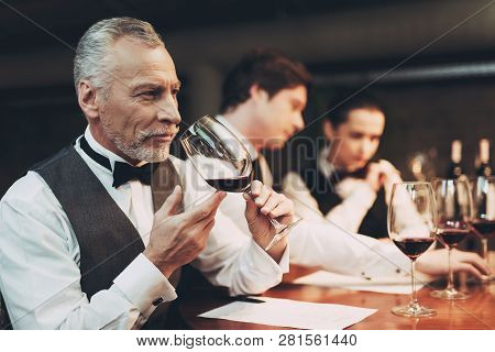 Two Male Sommeliers And Female Sommelier Make Up Wine List Sitting At Table With Glasses Of Wine. Co