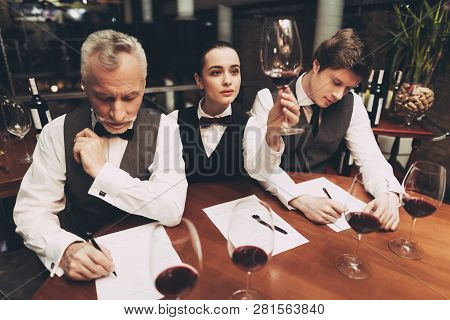 Beautiful Female Sommelier Is Holding Glass Of Wine And Tasting Sediments. Confident Sommelier Tasti