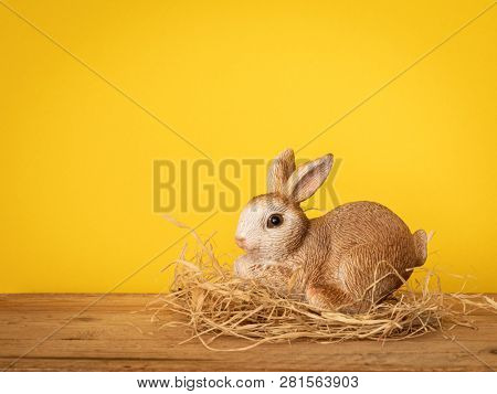 A sweet easter bunny figure yellow background