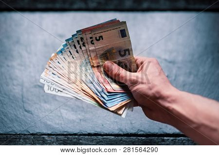 Hand´s Of Young Man Holding A Money. Banknotes On A Stone Background. Euro Money Bank Notes Of Diffe
