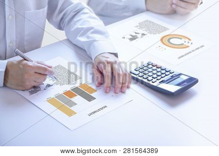 Businessmen Or Analyst In A Meeting Room Partially Cropped At Hands Holding A Pen On An Investment R