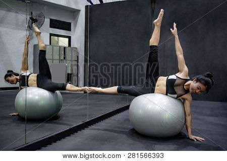 Young Asian Athlete Woman Doing Pilates Exercises With Exercise Ball In Fitness Gym. Healthy Lifesty