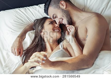 Happy Romantic Couple Embracing In The Bed - Young Lovers Having A Tender And Intimate Moments Looki