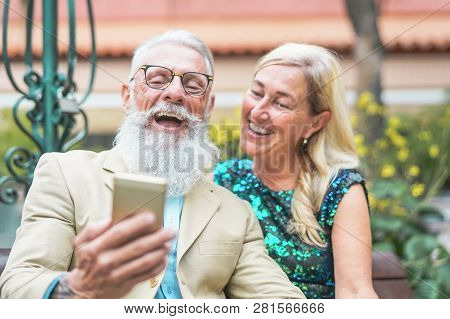 Happy Senior Couple Watching On Mobile Smart Phone And Laughing Together - Mature Fashion People Hav