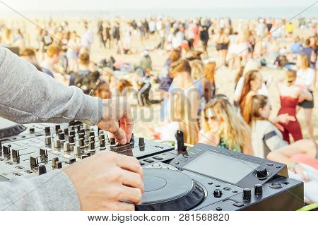 Close Up Of Dj's Hand Playing Music At Turntable At Beach Party Festival - Crowd People Dancing And