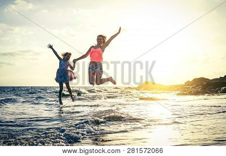 Happy Loving Family Of Mother And Daughter Jumping In The Water At Sunset On The Beach - Mom With He
