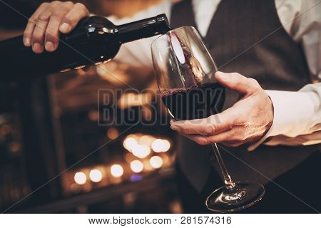 Close Up. Elegant Waiter Pours Red Wine From Bottle Into Glass At Restaurant. Sommelier Tasting Wine