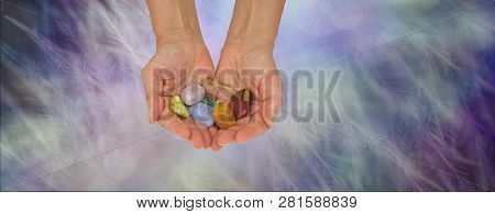 Crystal healing practitioner offering selection of tumbled healing stones - female crystal therapist with cupped hands filled with a variety of crystals on an ethereal feathered background with copy space poster