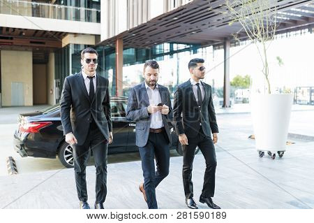 Businessman Using Smartphone While Walking With Bodyguards At Office Campus