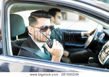 Attractive bodyguard planning safety measures with team using radio transceiver in car poster
