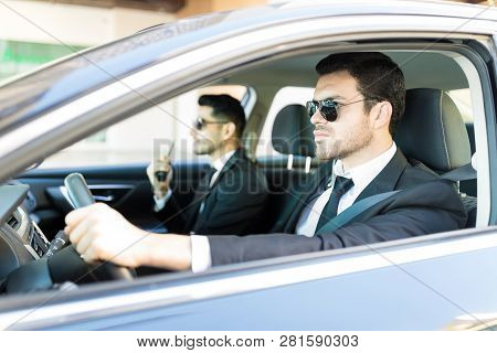Bodyguard Driving Luxury Car While Sitting By Colleague During Working Hours