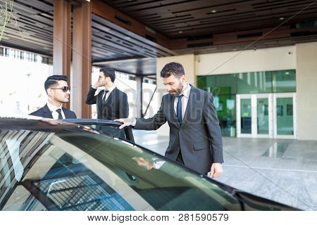 Mid Adult Ceo Entering Car While Young Bodyguards Serving Personal Protection